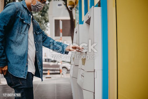 istock Young asian man wearing medical mask withdraw money from bank cash machine with debit card - Senior male doing payment with credit card in ATM - Concept of business, banking account and lifestyle people 1215074763