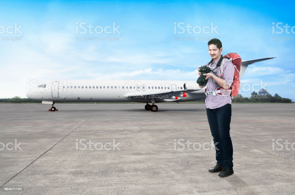 Young asian man with backpack and camera going traveling - Royalty-free Adult Stock Photo