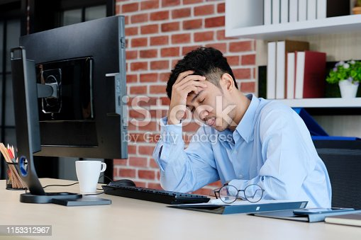 istock Young asian man with frustrated expression while working with computer at office desk, office lifestyle 1153312967