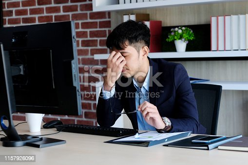 istock Young asian man with frustrated expression while working with computer at office desk, office lifestyle 1157926096
