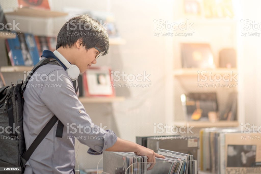 Young Asian man with headphones choosing phonograph disc in music shop stock photo
