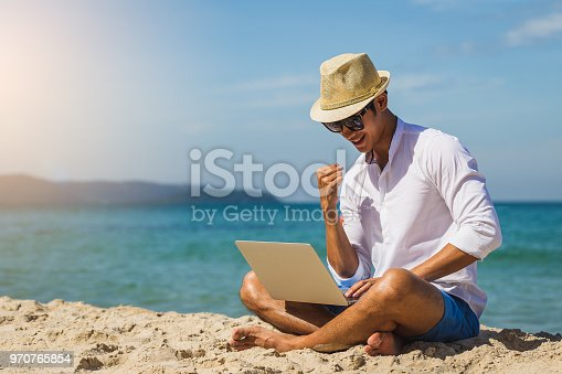 1043434558 istock photo Young Asian man with laptop computer working on the sea beach, internet, freelance, travel and vacation concepts, copy space 970765854