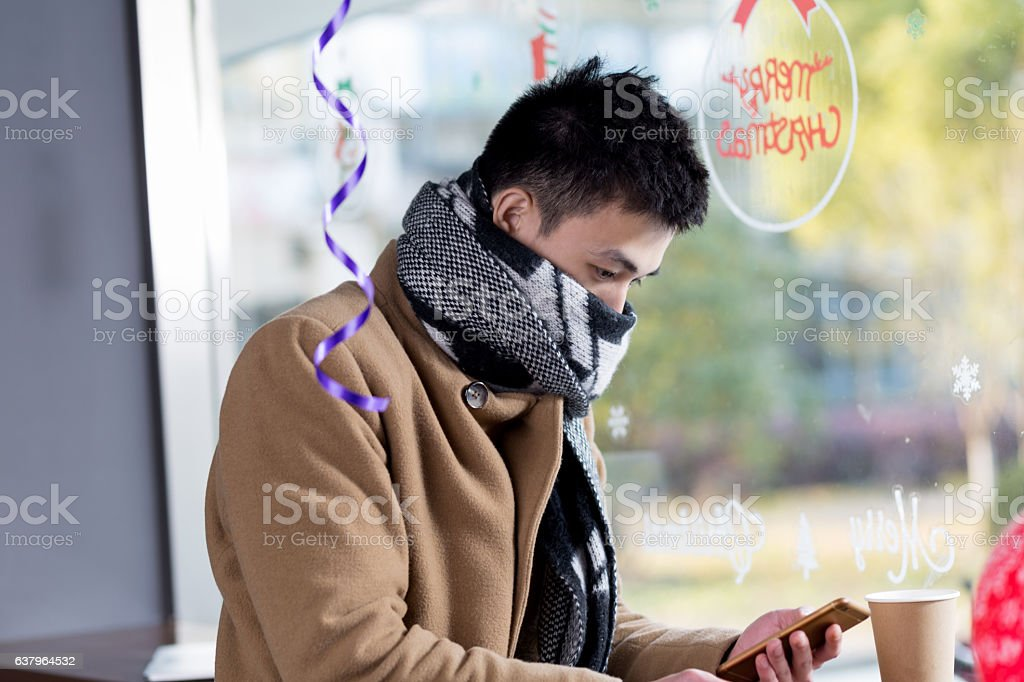 young asian man with mobile phone in cafe stock photo