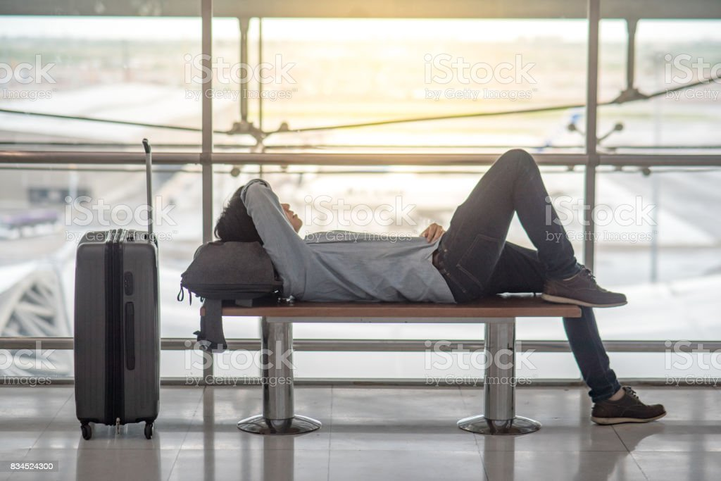 Young Asian man with suitcase luggage and backpack lying on bench in airport terminal stock photo