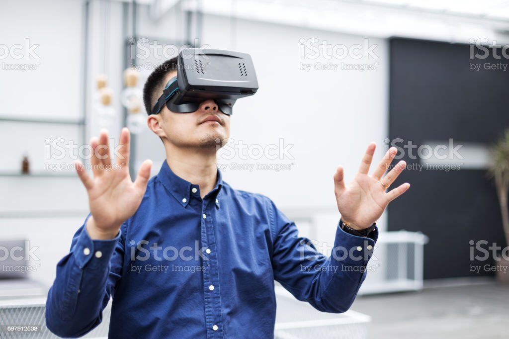 young asian man with VR in modern cafe stock photo