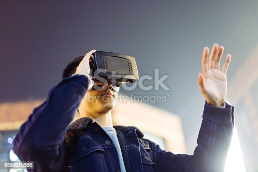 istock young asian man with VR on street at night 635831886
