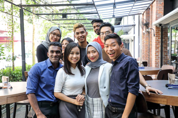 Young Asian man woman group portrait colleague student friend family stock photo