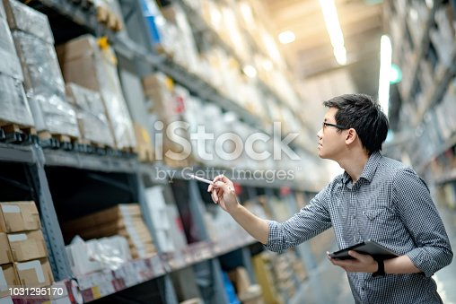 istock Young Asian man worker doing stocktaking of product in cardboard box on shelves in warehouse by using digital tablet and pen. Physical inventory count concept 1031295170