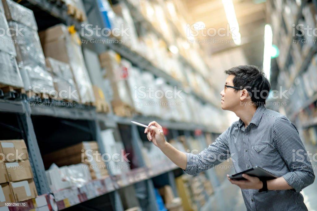 Trabajador joven asiático haciendo inventario de producto en caja de cartón en estantes de almacén mediante el uso de lápiz y la tableta digital. Concepto de recuento de inventario físico - foto de stock