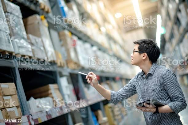 Jonge Aziatische Man Werknemer Doen Inventarisatie Van Product In Kartonnen Doos Op De Planken In Magazijn Met Behulp Van Digitale Tablet En Pen Fysieke Inventaris Tellen Concept Stockfoto en meer beelden van Alleen mannen