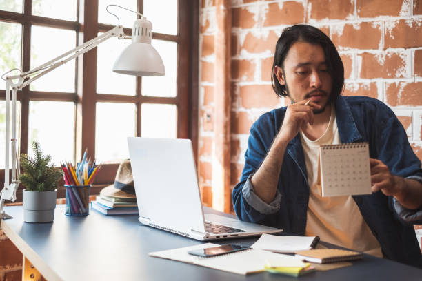 Young Asian man working on laptop for business creative designer stock photo