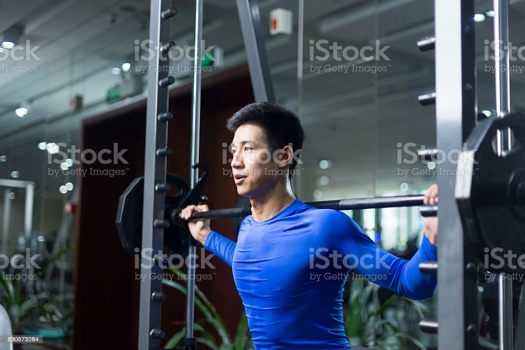 young asian man working out in modern gym stock photo
