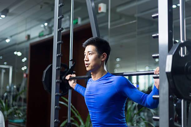 若いアジア人男性のモダンなジムでワークアウト ストックフォト