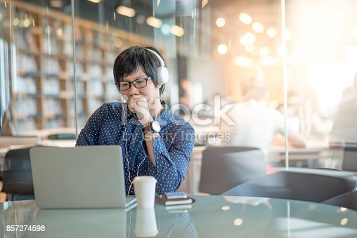 istock Young Asian man working with his laptop computer in public library 857274598