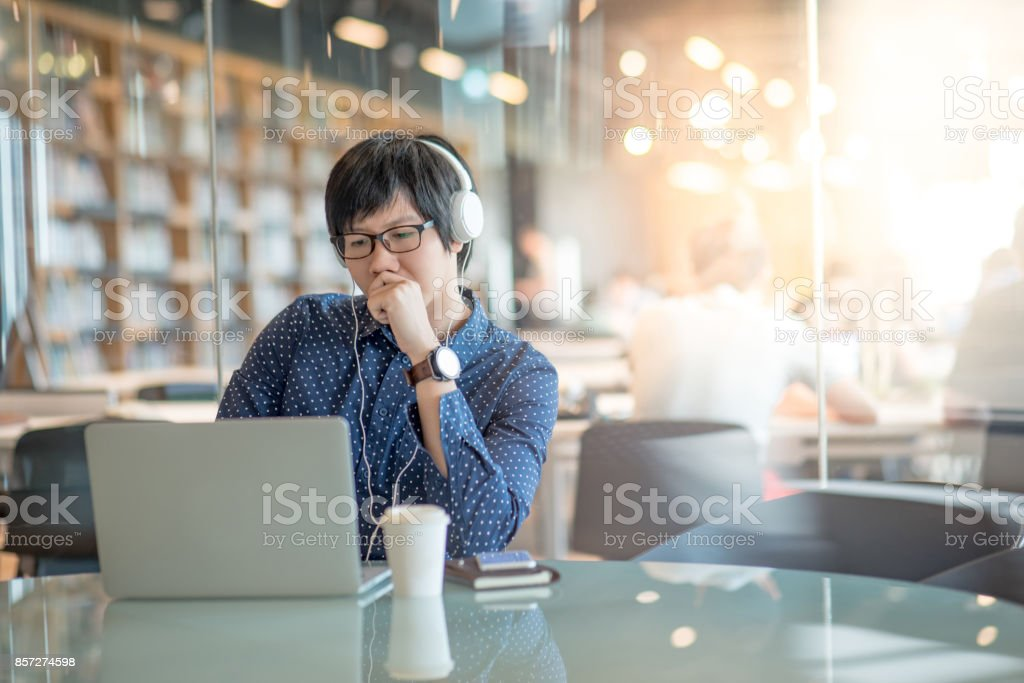 Young Asian man working with his laptop computer in public library stock photo