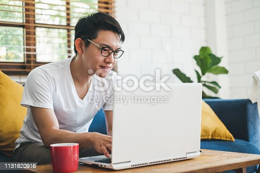 Young Asian man working with laptop at home