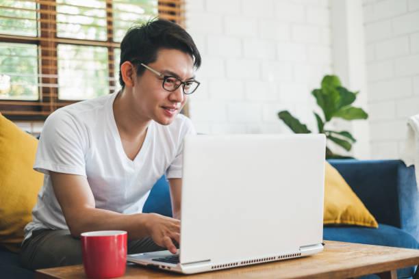 在家裡使用筆記本電腦工作的年輕亞洲人 - 亞洲 個照片及圖片檔