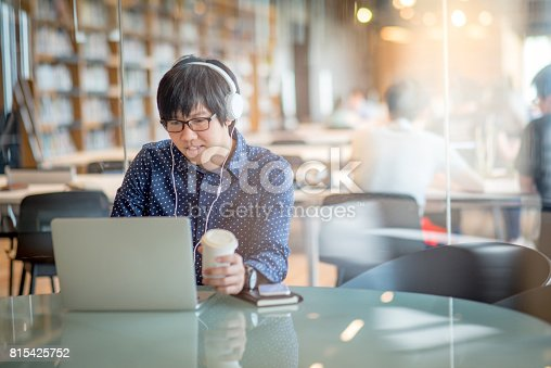 istock Young Asian man working with laptop computer and holding coffee cup 815425752