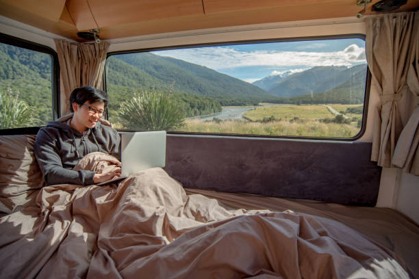 young asian man working with laptop computer on the bed in camper van - asian travel in car stock photos and pictures