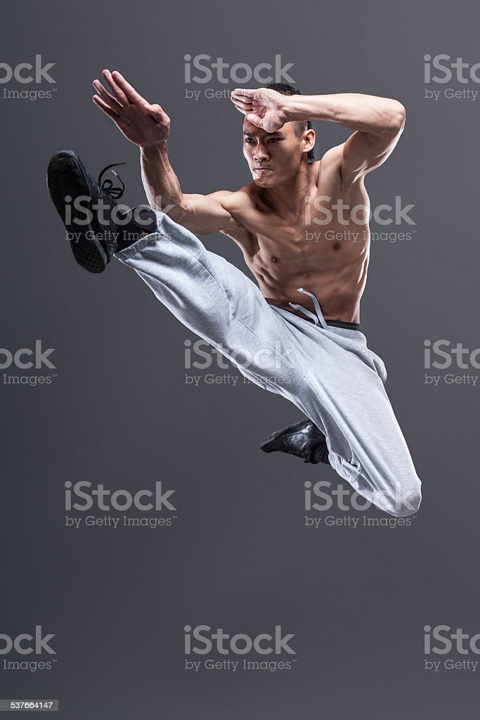 Young asian man workout over grey background karate jump kick stock photo
