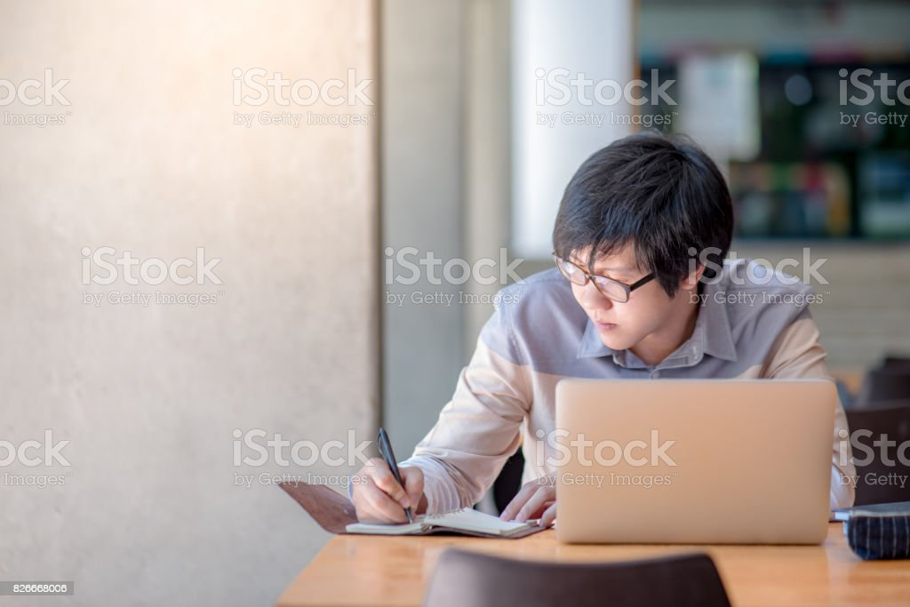 Young Asian man writing on notebook and working with laptop computer in college building stock photo