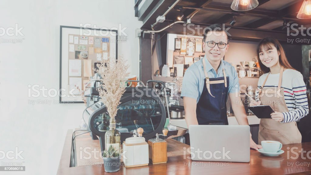 Young Asian man&woman barista wear apron using laptop with coffee cup served to customer at bar counter in coffee shop with smile face.Concept of cafe and coffee shop small business.Vintage tone stock photo