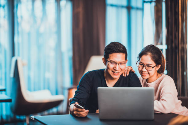 young asian married couple working together using laptop at home or modern office with copy space. startup family business, sme entrepreneur, business partner, love relationship, or freelance concept - east asian ethnicity stock photos and pictures
