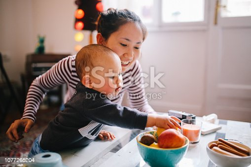 Brightly lit image of a young Thai mom with her little baby boy. They're spending time together at home, playing with toys and having some snacks. Asian family lifestyle concepts, shot in Europe.