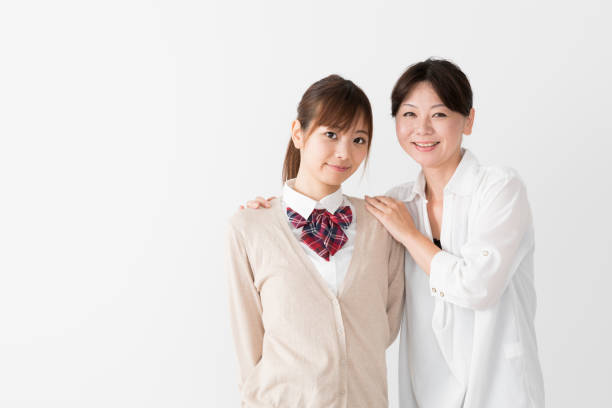 young asian mother and daughter on white background young asian mother and daughter on white background japanese school girl stock pictures, royalty-free photos & images