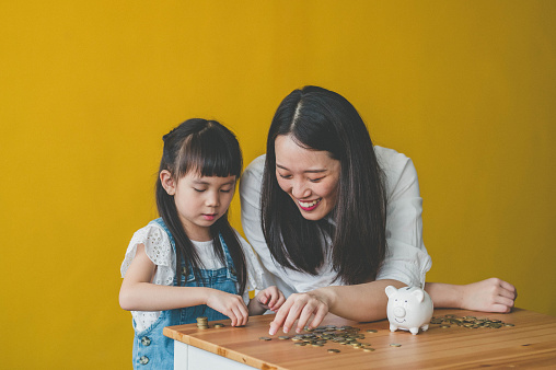 Young Asian Mother and her daughter count coins from piggy bank.