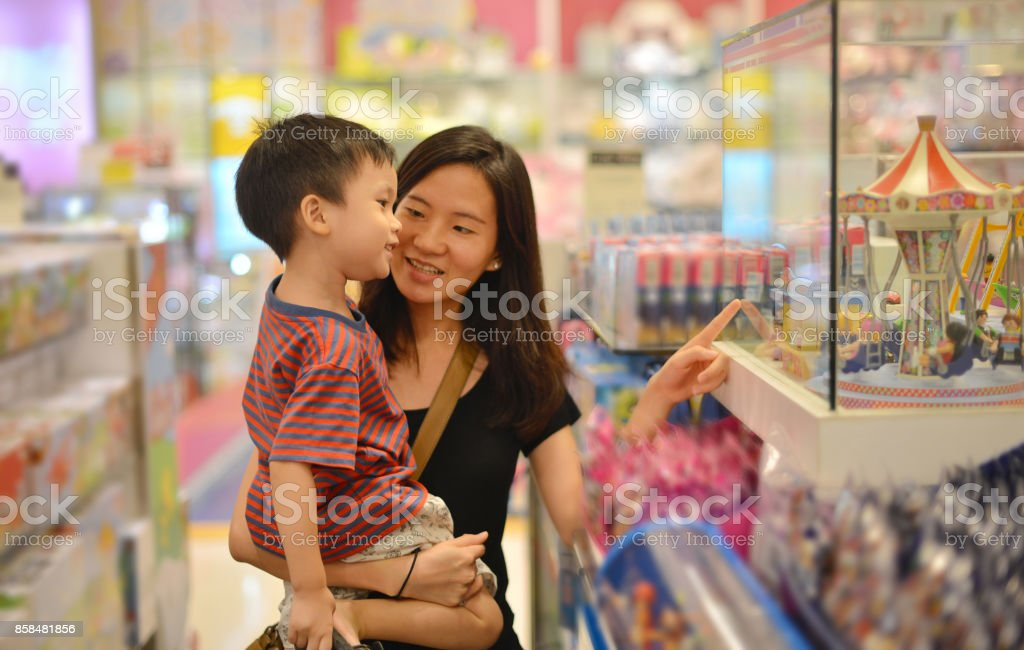 Young Asian mother and her kid shopping toy in shopping mall stock photo