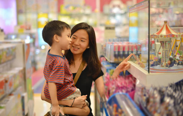 Young Asian mother and her kid shopping toy in shopping mall Young Asian mother and her kid shopping toy in shopping mall thailand mall stock pictures, royalty-free photos & images
