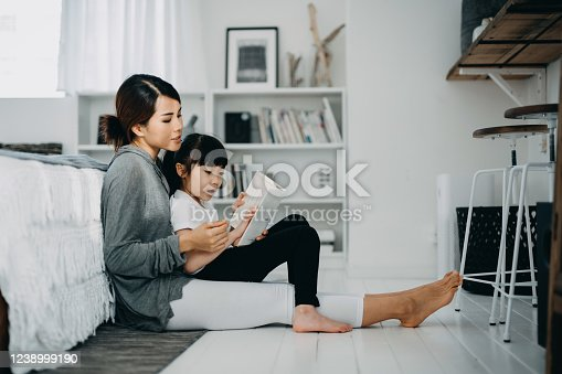 Young Asian mother sitting on the floor in the bedroom reading book to little daughter, enjoying family bonding time together at home