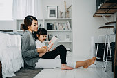 istock Young Asian mother sitting on the floor in the bedroom reading book to little daughter, enjoying family bonding time together at home 1238999190