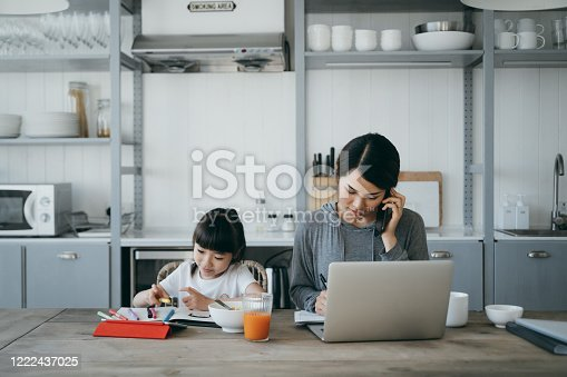 Young Asian mother working from home on a laptop and talking on the phone while little daughter is studying from home. She is attending online school classes with a digital tablet and doing homework at home