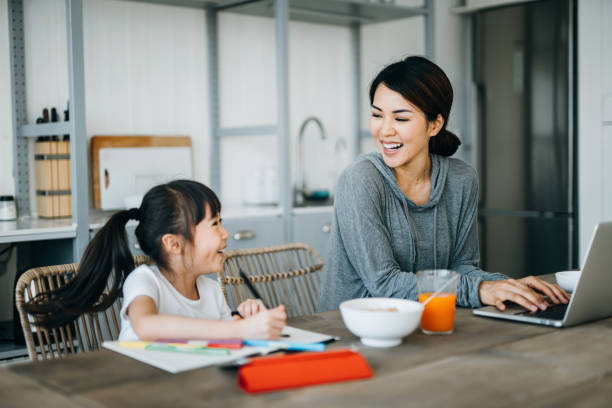 Young Asian mother working from home on a laptop while little daughter is studying from home. She is attending online school classes with a digital tablet and doing homework at home
