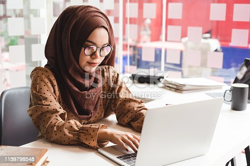 Young asian muslim business woman in smart casual wear working with laptop computer while sitting in the creative cafe.