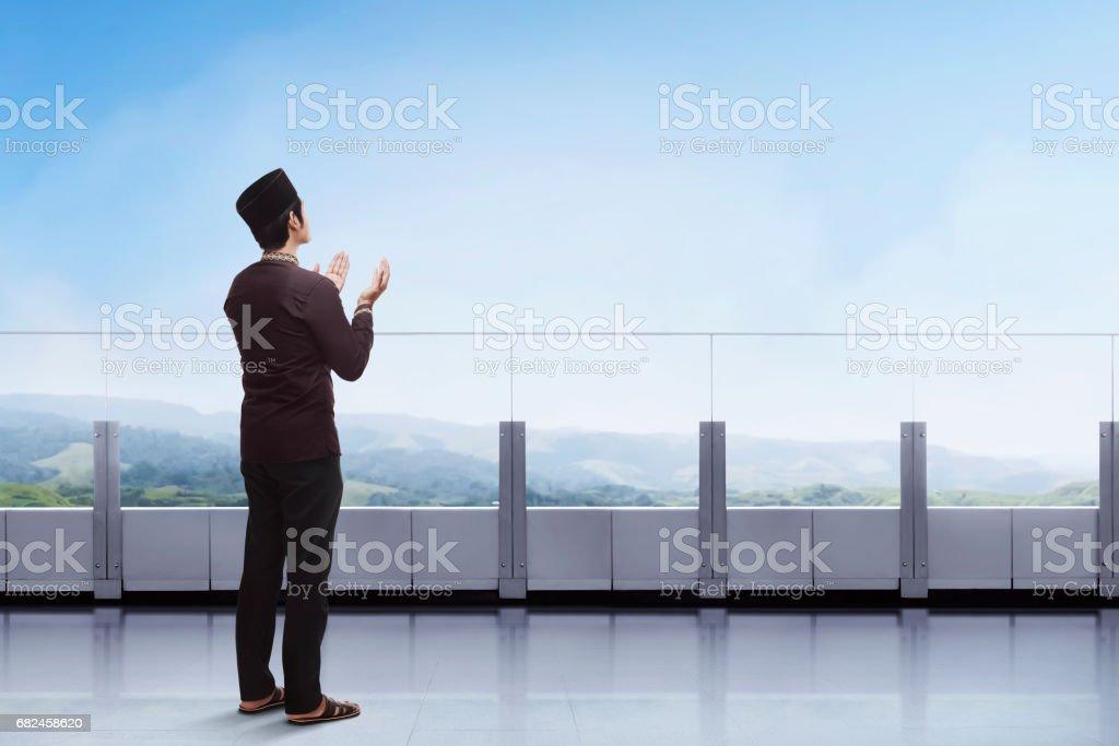 亞洲年輕穆斯林男子祈禱與舉手示意,在陽臺上 免版稅 stock photo