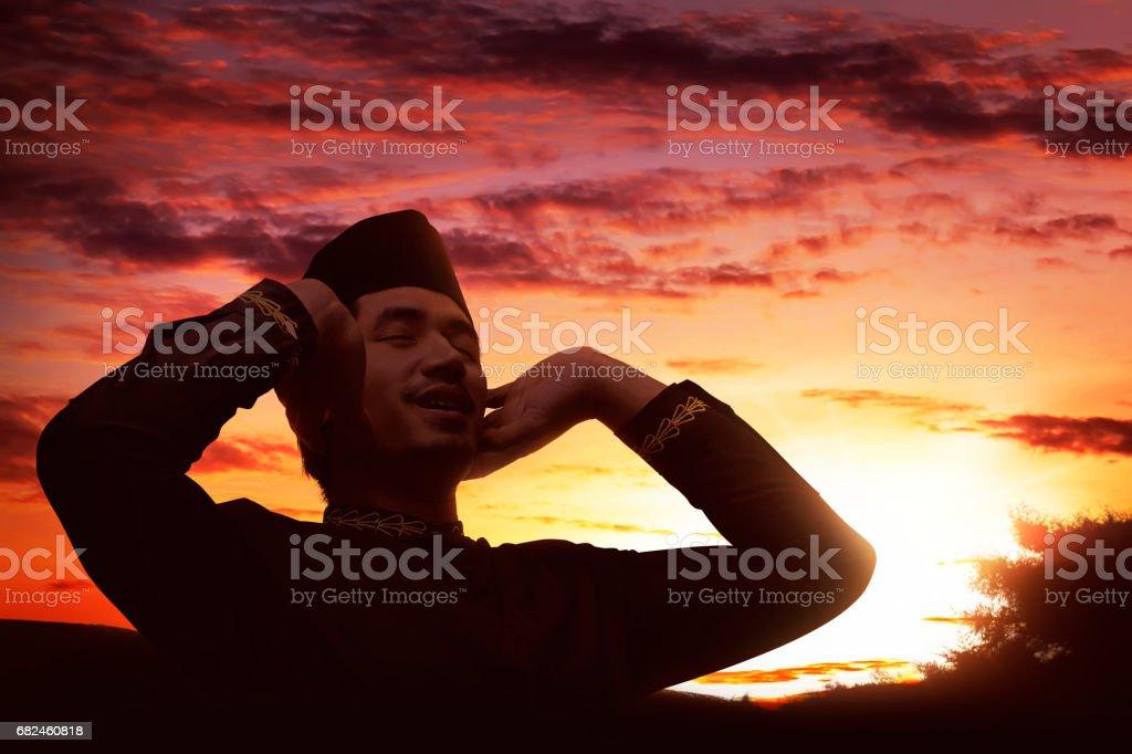 Young asian muslim man praying with raising hand Стоковые фото Стоковая фотография