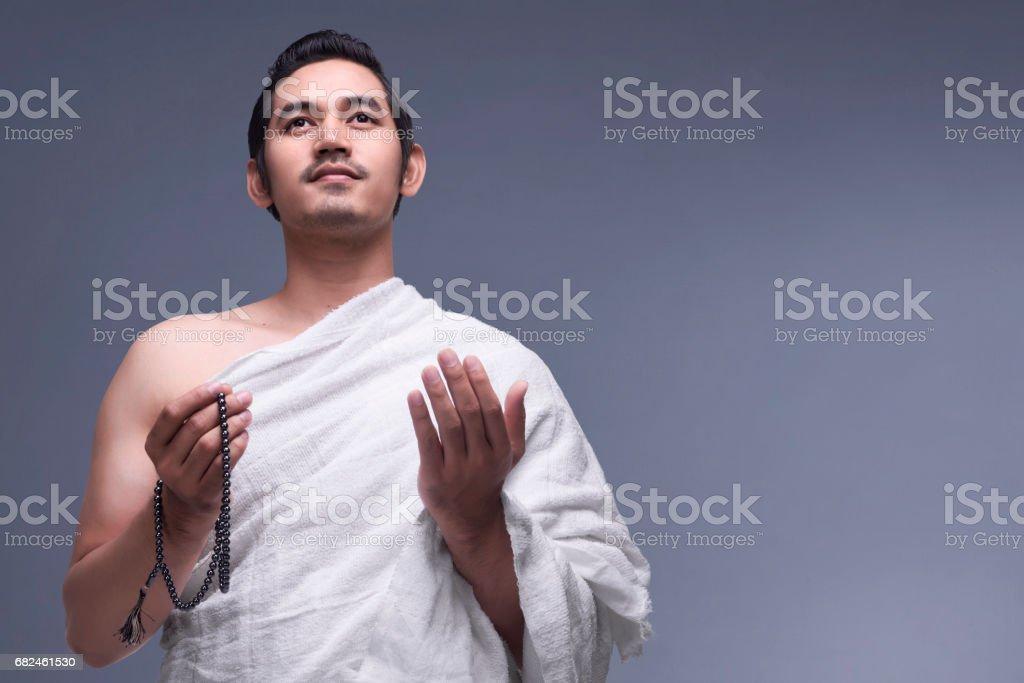 Genç Asyalı Müslüman adam İhram kıyafetlerle tespih ile royalty-free stock photo