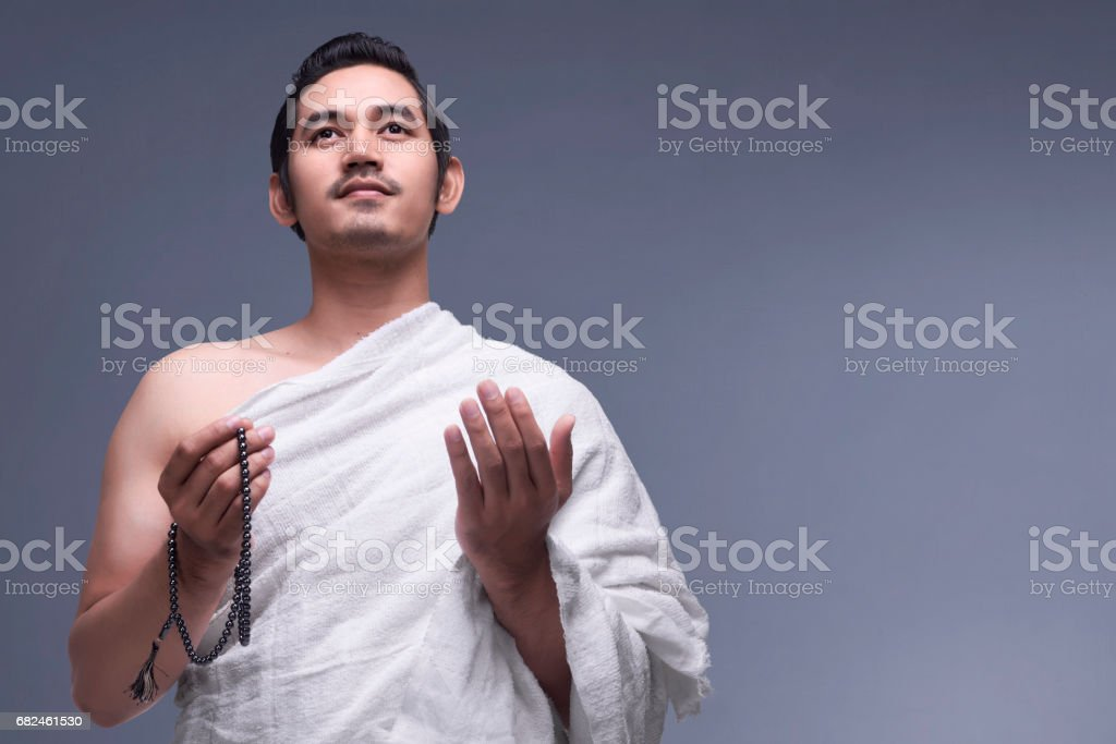 Young asian muslim man wearing ihram clothes with prayer beads stock photo