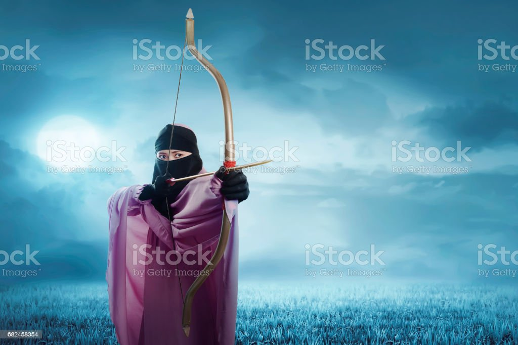 Young asian muslim woman in hijab ready to shoot an arrow royalty-free stock photo
