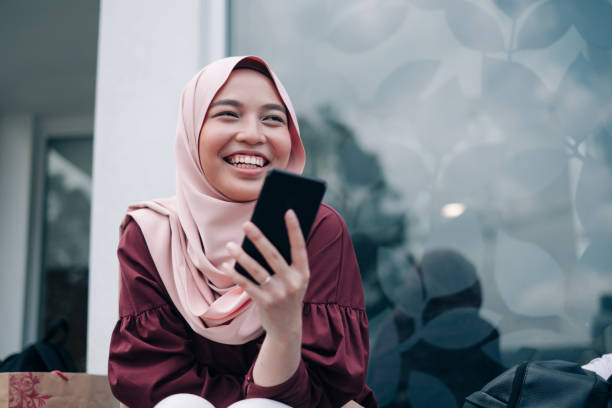 jovens mulheres muçulmanas asiáticas jogando smartphone - malásia - fotografias e filmes do acervo