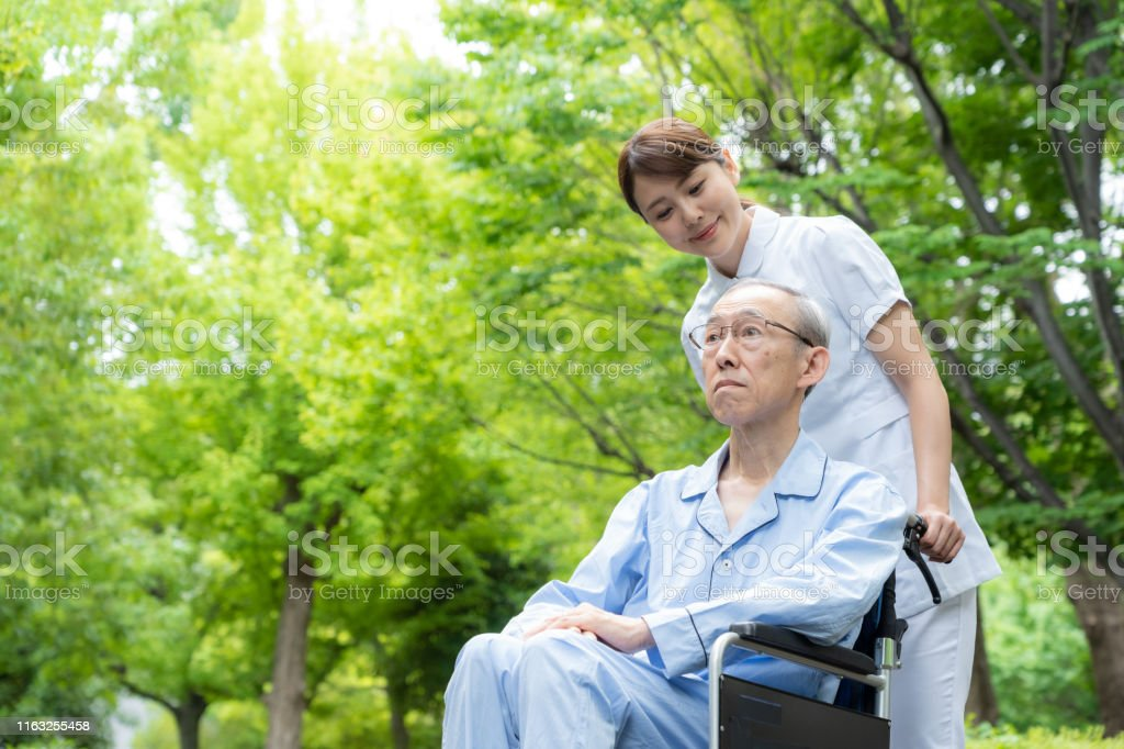 young asian nurse and old asian patient with wheelchair in park