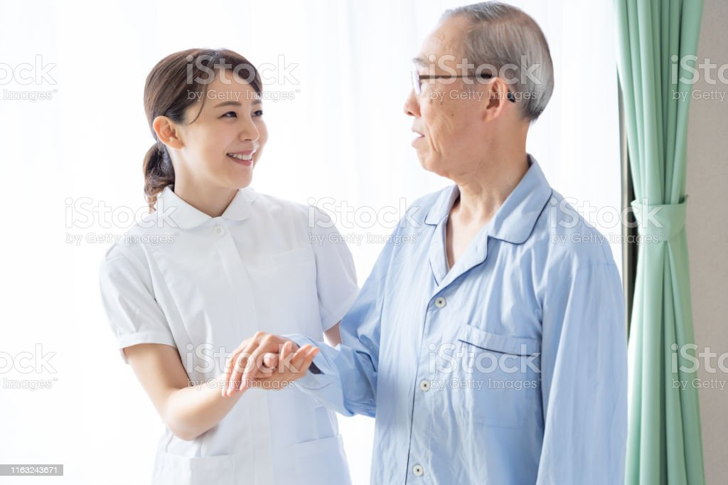 young asian nurse with old asian patient in hospital