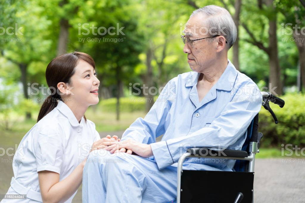 young asian nurse with old asian patient in park
