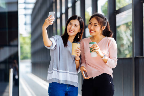 young asian people taking selfie photos together inside the glass building - beautiful college girl pics stock photos and pictures