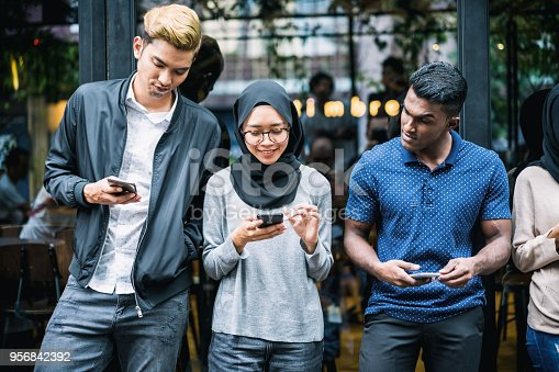 Small group of young adult using smartphones for communication.