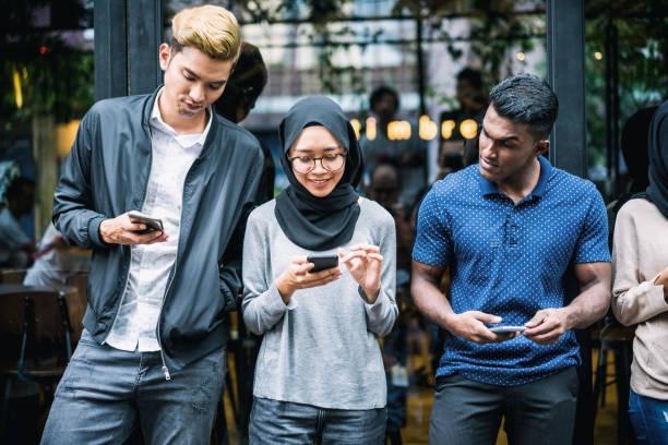 jovens asiáticos usando smartphones - malásia - fotografias e filmes do acervo