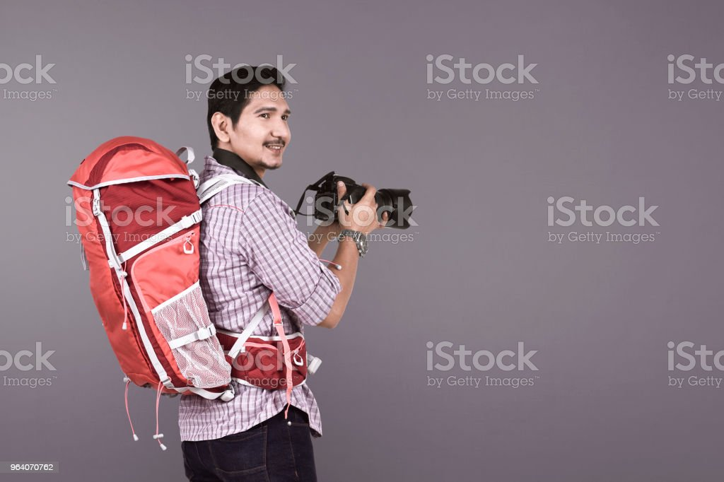 Young asian photographer with backpack holding camera - Royalty-free Adult Stock Photo